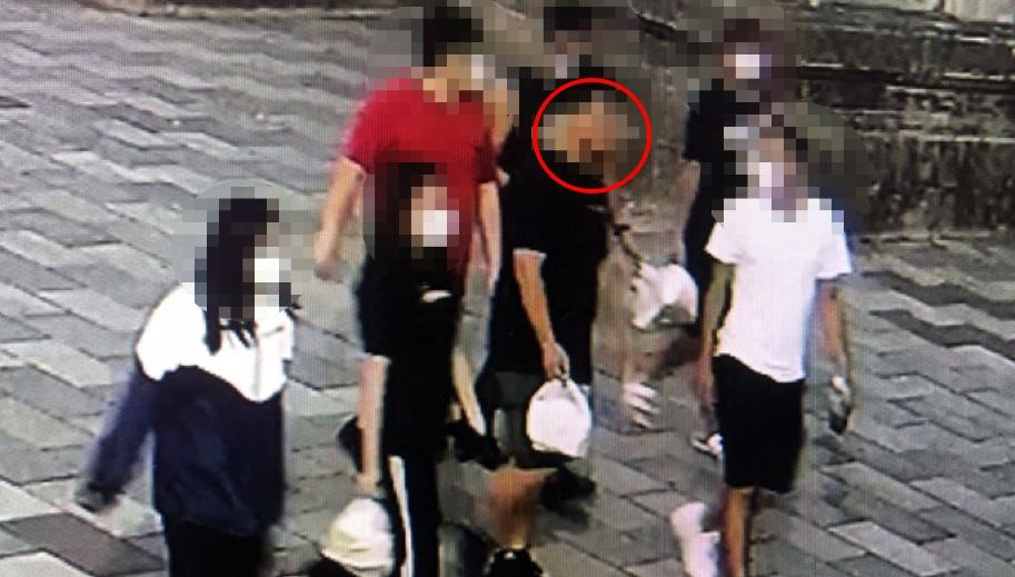 一群年經人群聚,紅圈處男子未戴口罩。圖/台視新聞