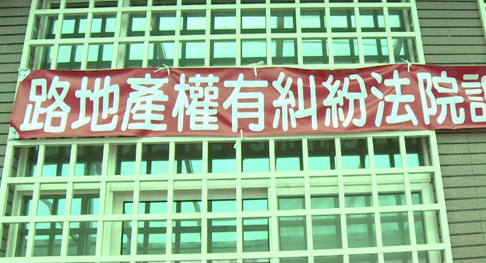 原住戶在房屋上掛起紅布條,控訴建商。圖/台視新聞