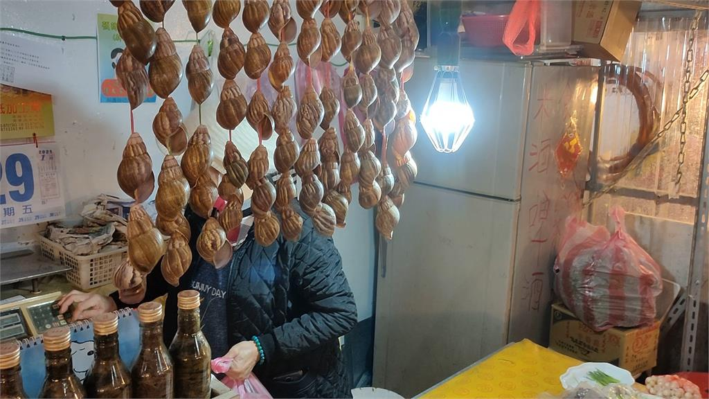 攤販除了把蝸牛肉裝包販售,也把蝸牛殼串起擺設攤位。圖:台視新聞
