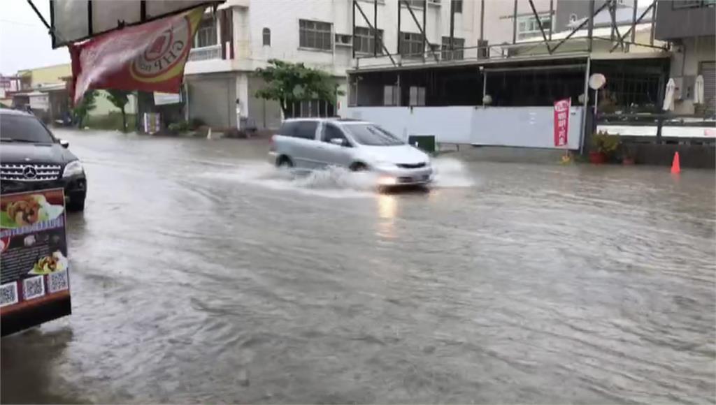 路面淹水,車輛行經幾乎整個輪胎泡在水裡。圖/台視新聞