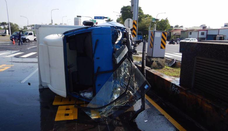 貨車撞上分隔島後側翻,擋風玻璃掉落。圖:台視新聞